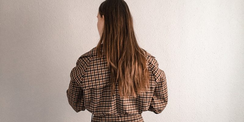 girl standing on front of a white wall in checkered clothes