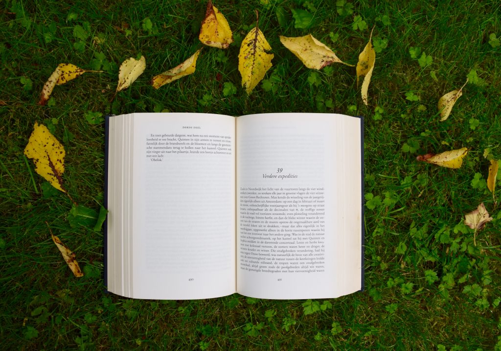 Open book laying on green grass surrounded by leaves