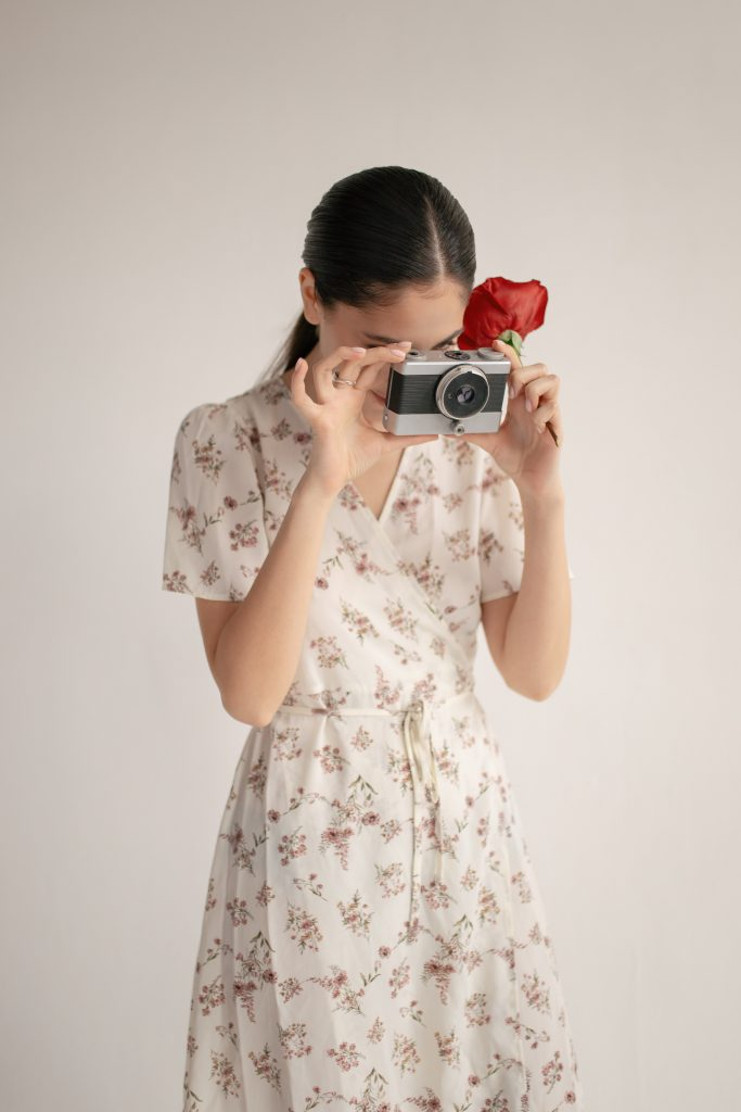 girl in dress taking picture with old camera