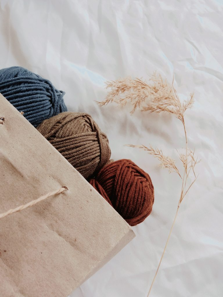three pieces of yarn, one blue, one red and one brown all placed in a brown paper back