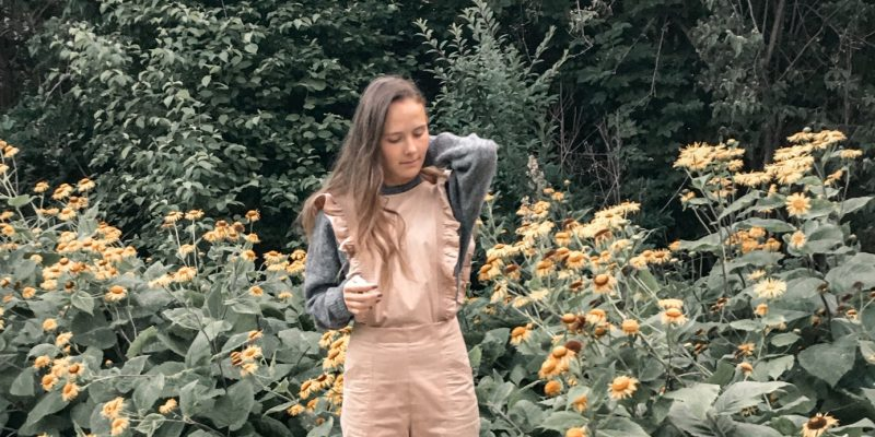 girl standing in ethical jumpsuit in front of yellow flowers